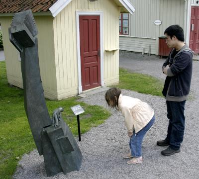 Angela och Alexander kollar en staty i Örebros stadspark